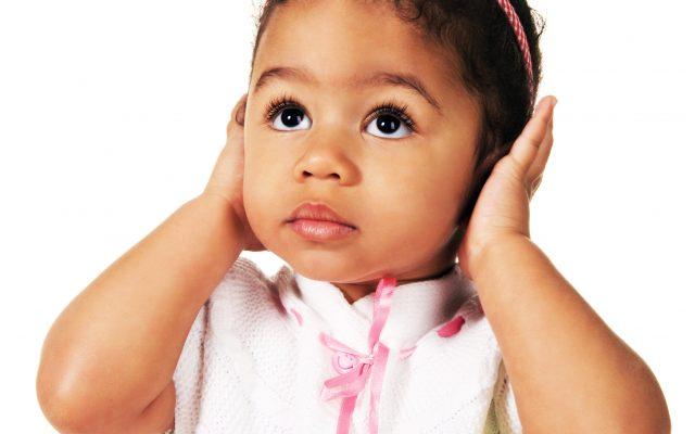 Cute little girl shutting dawn her ears, white background